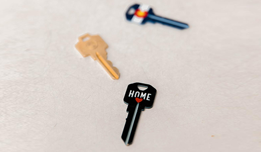 Close up of three house keys resting on a table