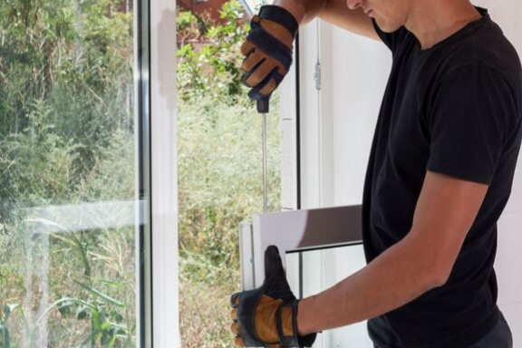 A professional window technician installing a replacement window