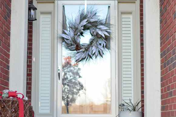 Close up of a wintery front porch with a storm door
