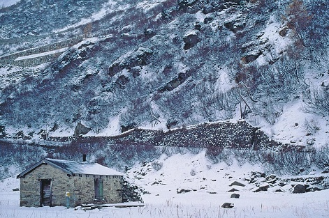A small cottage surrounded by snow