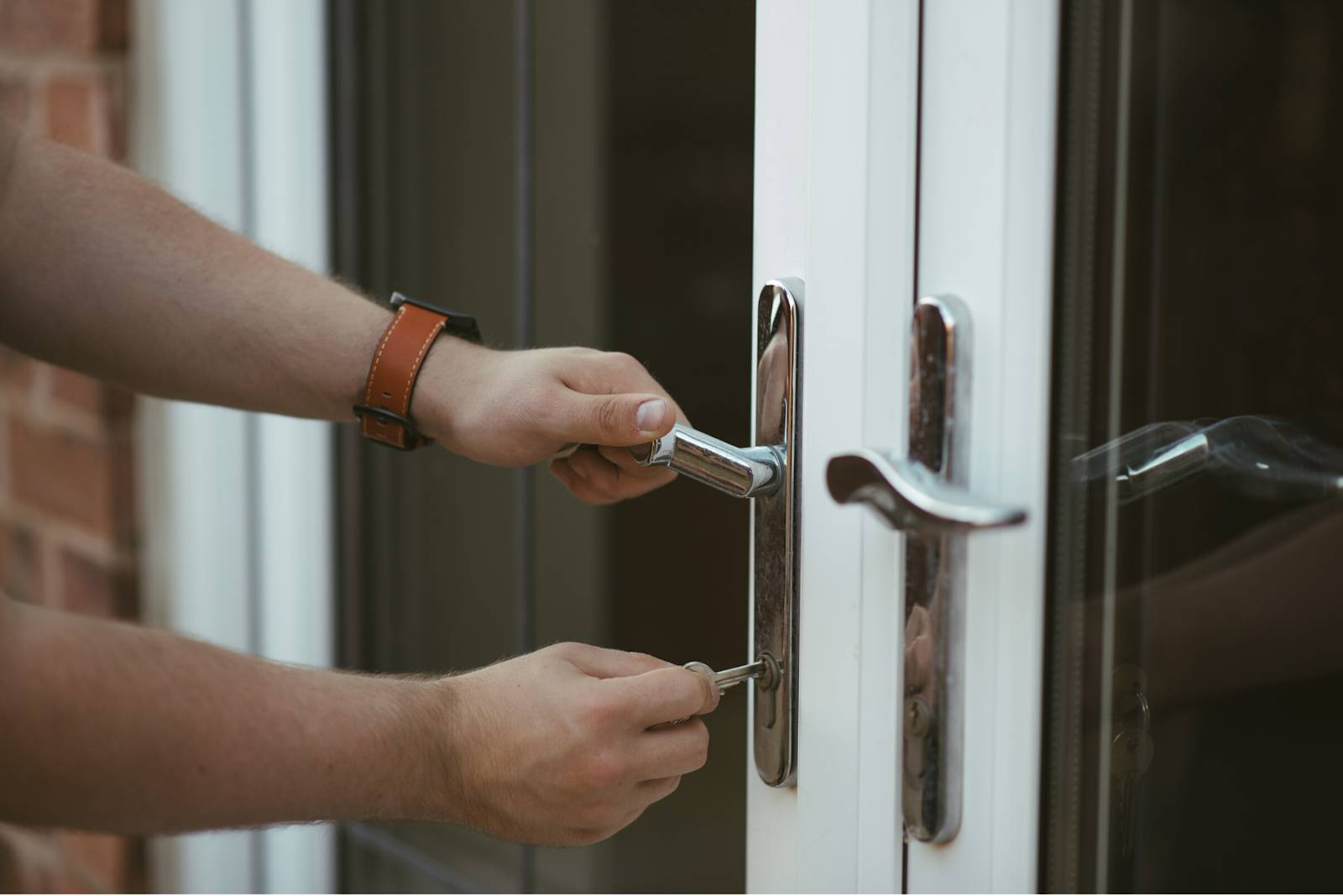 Close up of a man unlocking his front entry door