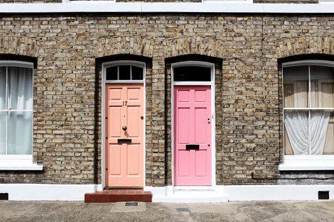 Two doors next to each other in the brick neighbourhood.