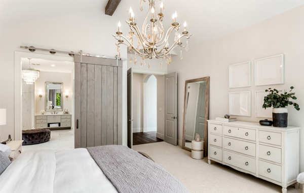 Elegant bedroom with a barn door opening to the powder room