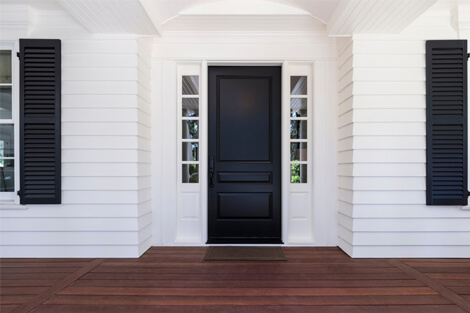 Black front door against classic white wal