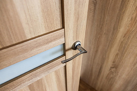 A finished wooden door with a silver handle