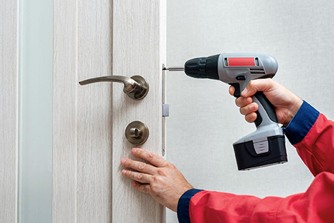 Closeup of a man installing the locks on a brand new door