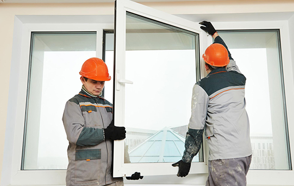 Two workers installing brand new windows to a house