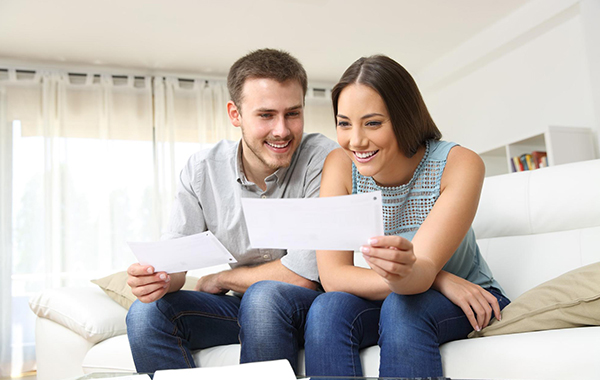 Happy young couple looking at their energy savings