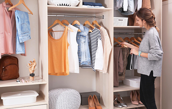 Woman looking through a tidy closet with multiple shelves