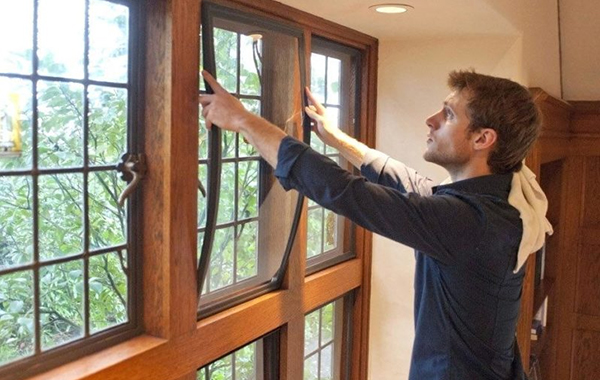 Man installing window inserts to his windows