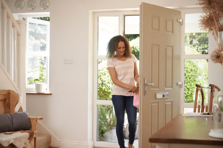 A woman opening the front door of a house
