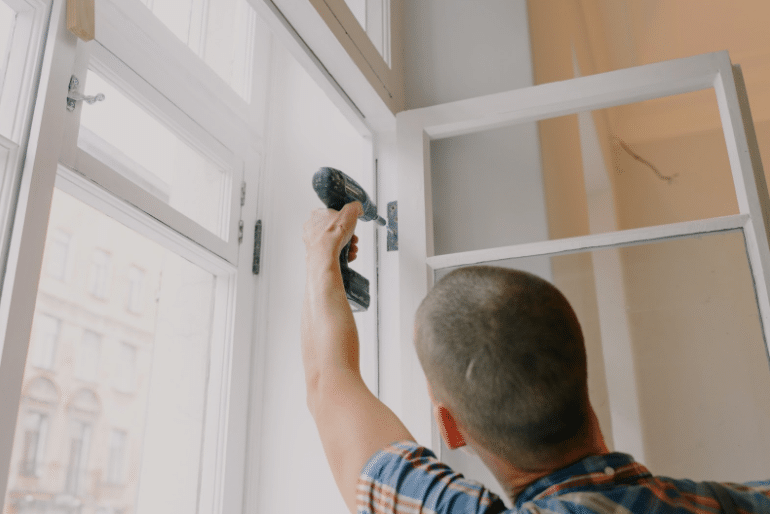 A man drilling a window into place