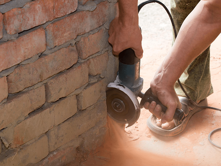 Close up of a man using a hand-held saw to cut a brick wall