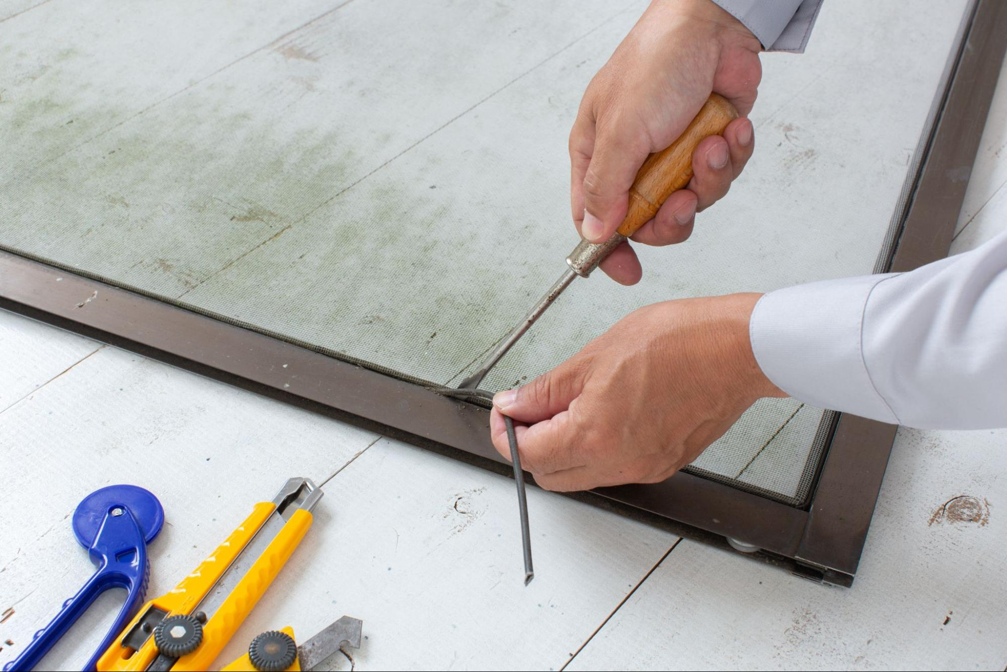 Close up of a man's hands removing the old spline of a screen door using a screwdriver