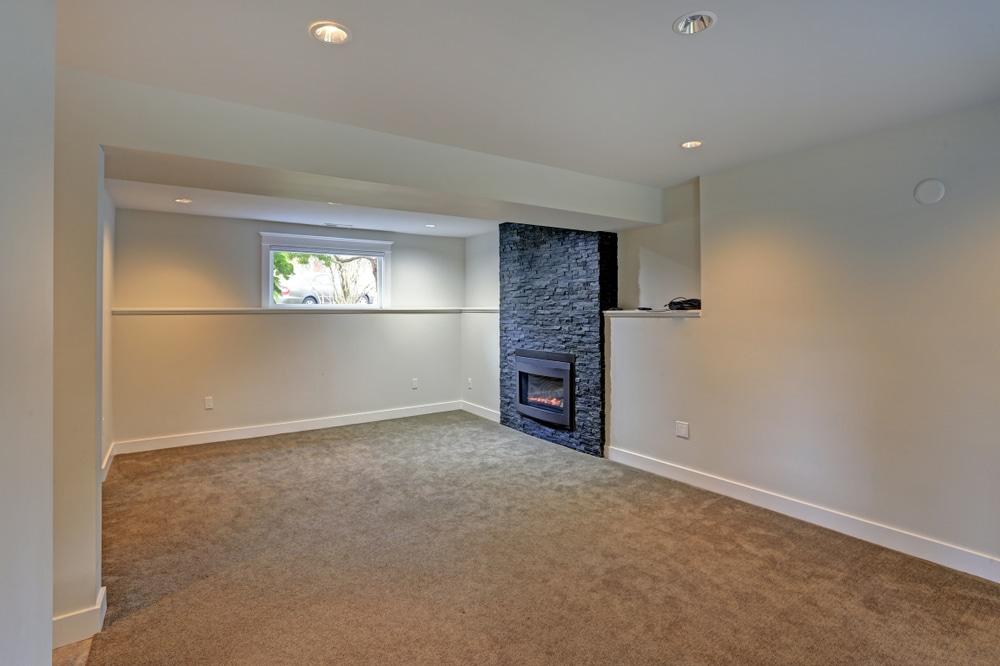 An empty basement with a window and a fireplace