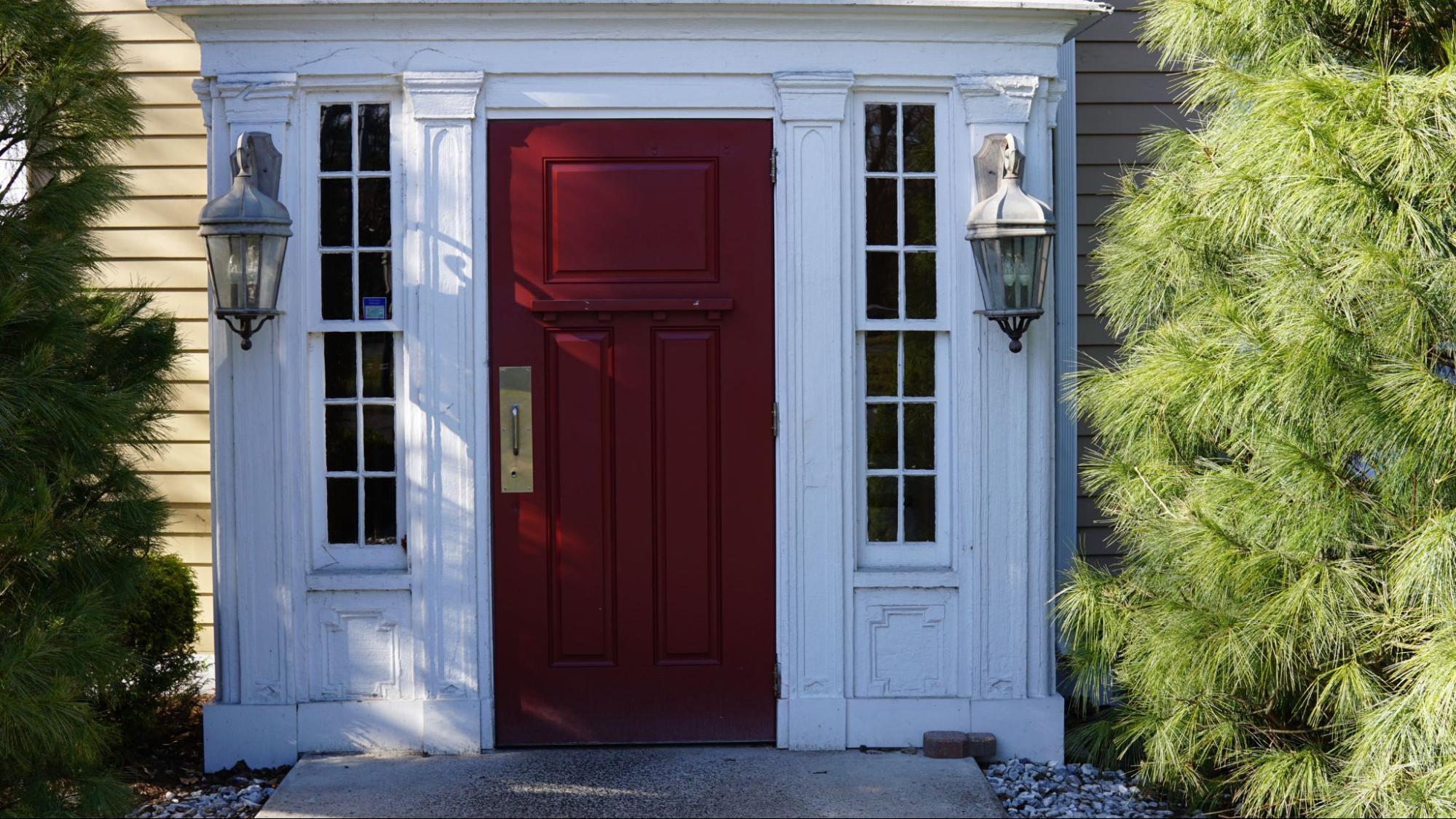 A red solid wood door amidst the white facade of a house